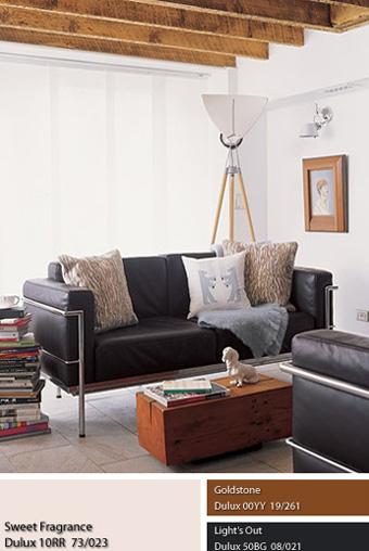 Chiếc trường kỷ phủ da màu đen tạo độ tương phản với những bức tường sơn màu trắng Dulux Sweet Fragance hư không của căn phòng.
