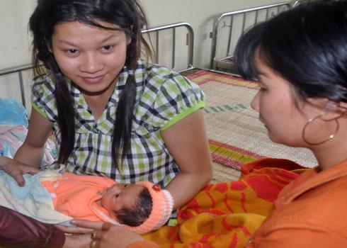 Sản phụ Trần Thị Hồng Cẩm vui mừng bên con gái của mình sau gần hai ngày bị trao nhầm là bé trai của của chị Hoái. Ảnh: Trí Tín