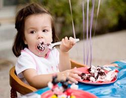 Cha mẹ nên tập cho bé tự múc đồ ăn, không nên sợ bé làm đổ. Riêng đối với thức ăn nóng, cha mẹ nên thổi để làm mát trước khi cho trẻ dùng. Ảnh: thegioitretho.