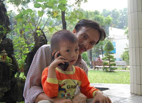 Em Trần Khánh Bình bị hở hàm ếch, cùng ba là Trần Duy Thái, bắt xe đò từ Tây Ninh đến Sài Gòn từ tờ mờ sáng cho kịp khám sàng lọc. Em Bình nói chuyện với bà nội qua điện thoại ;