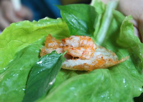 Bánh khọt được cuốn với các loại rau, chấm vào chén nước chấm và thưởng thức.