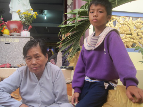 """Bé trai 9 tuổi Nguyễn Ngọc Hiển cùng bà nội của mình là Nguyễn Thị Bảy, 74  tuổi. Cả hai bà cháu đều đăng ký khám bệnh đợt này. """"Mấy hôm nay tôi đau nhức suốt, nghe có bác sĩ về nên ráng đợi đến hôm nay để được khám bệnh"""", bà Bảy chia sẻ."""