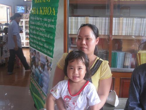 Bé Huỳnh Thị Như Ý, 4 tuổi được mẹ dỗ dành khi ngồi chờ đến lượt nhổ răng.
