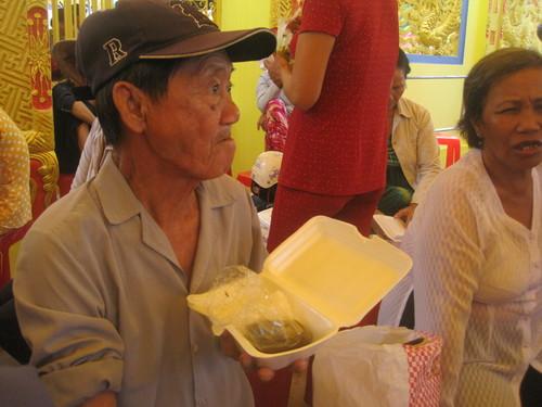 Đi từ sáng sớm nhưng số thứ tự khá lớn nên ông Ngà, 78 tuổi nhận hộp cơm miễn phí ăn quá trưa để đợi đến chiều. Ông  bị đau nhức xương khớp, cao  huyết áp đã lâu.