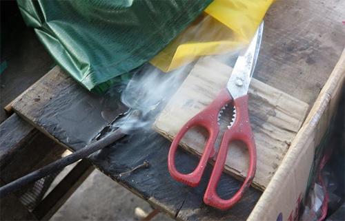 Sau khi chiếc dùi được nung đỏ, ông Sĩ lấy ra và chà qua nến để giảm nhiệt đến nhiệt độ sao cho khi đưa vào ni lông không bị cháy và giúp chiếc dùi trơn hơn