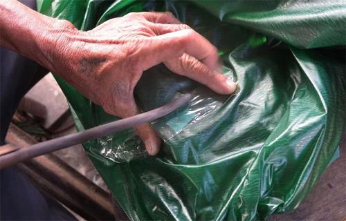 Miếng vá nhỏ bằng ni lông cùng loại với áo mưa được đặt lên lỗ thủng, sau đó ông lấy 1 miếng ni lông khác loại không dính đặt lên trên, dùng dùi tạo ra nhiệt cho miếng vá dính vào áo mưa.