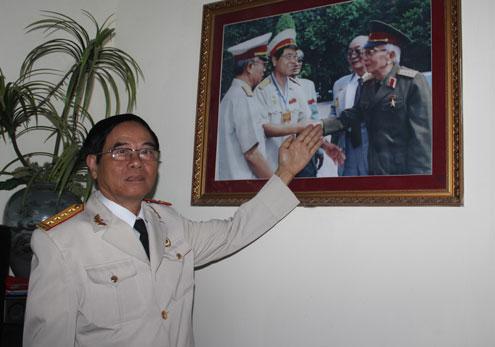 Ông Hiến mặc quân phục chỉnh tề đứng cạnh bức ảnh chụp cùng Đại tướng Võ Nguyên Giáp năm 1982. Bức ảnh được gia đình ông treo trang trọng trong phòng khách.