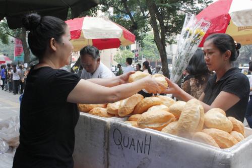 Nhiều người dân Hà Nội phục vụ bánh mì, nước miễn phí cho bà con đứng xếp hàng đi viếng Đại tướng. Ảnh: Phan Dương.