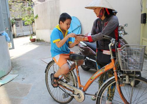Hình ảnh cậu bé có khuôn mặt kháu khỉnh, đáng yêu được người mẹ chở bằng xe đạp. Ảnh: Lê Phương.