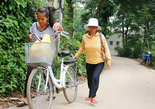 Hàng ngày cô bé Nhàn vẫ đèo mẹ trên chiếc xe đạp rong ruổi quanh các tuyến phố để bán vé số. Ảnh: Phúc Nguyễn