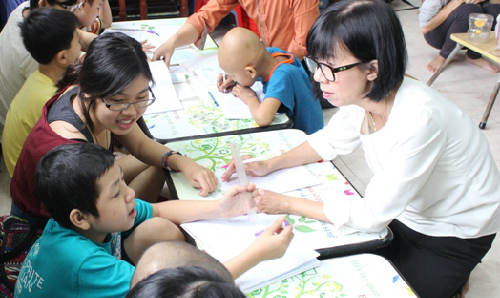 """5 năm nay, hằng trăm trẻ """"đầu trọc"""" tại BV Ung bướu TP HCM được cô giáo Đinh Thị Kim Phấn (áo trắng) và các tình nguyện viên âm thầm dạy dỗ. Ảnh: Lê Phương."""