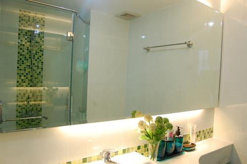 Màu xanh ùa vào không gian phòng tắm qua những chi tiết trang trí giản đơn. Việc giấu nhà tắm sau tủ quần áo tạo cảm giác thoải mái khi vào phòng ngủ.