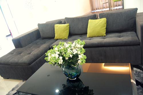Màu đen từ bộ salon ở phòng khách kết hợp gốm ôm và hoa trang trí màu xanh lá đạt hiệu ứng giúp căn phòng vừa sang trọng nhưng vẫn tươi mát và bắt mắt.
