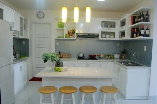 Theo kiến trúc sư Hoàng Hoài Sơn từ SogiArt, phòng bếp của căn hộ đã được nâng lên để nhìn căn nhà co chiều sâu và rộng hơn so với một mặt bằng như căn hộ cũ. Những chiếc ghế gỗ nhỏ xinh kê trước gian bếp để tiếp khách, tự nhiên và gần gũi....