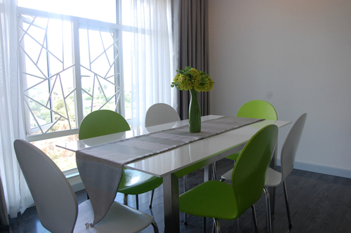 Căn phòng  trong căn hộ trên đường Nguyễn Hữu Thọ, Nhà Bè, TP HCM đón nắng bên cửa sổ mát dịu với những chiếc ghế tựa trắng, xanh kê xen kẽ và một lọ hoa xinh màu xanh lá.