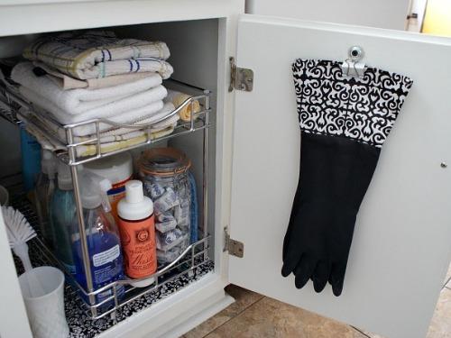 Đây là mẹo nhỏ giúp căn bếp chật chội được ngăn nắp hơn. Găng tay cần thiết khi làm vườn hay rửa bát đĩa được kẹp gọn bên trong nhờ mấu nhỏ của chính cánh cửa nhằm tiết kiệm diện tích.