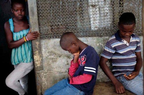 Promise Cooper, 16 tuổi, Emmanuel Junior Cooper, 11 tuổi và Benson Cooper, 15 tuổi, ngồi bên ngoài ngôi nhà của các em tại Liberia. Cha mẹ và em trai 5 tháng tuổi đã chết vì Ebola. Một người em khác, Ruth (13 tuổi) đang dần khỏe lại tại khu vực điều trị cách ly. Ảnh: AP