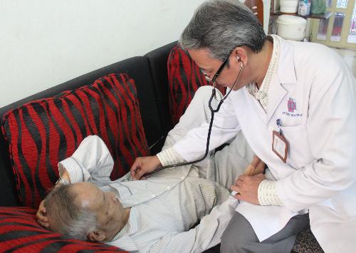 Bác sĩ Vũ Ngọc Trác đến khám bệnh tại nhà cho cụ ông 90 tuổi. Ảnh: Lê Phương.