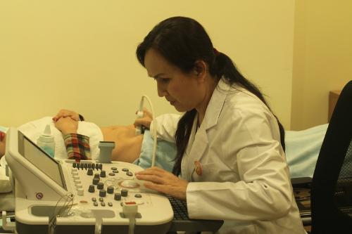 Bác sĩ Từ Vân đang thực hiện siêu âm bụng tại phòng khám được trang bị thiết hiện đại.