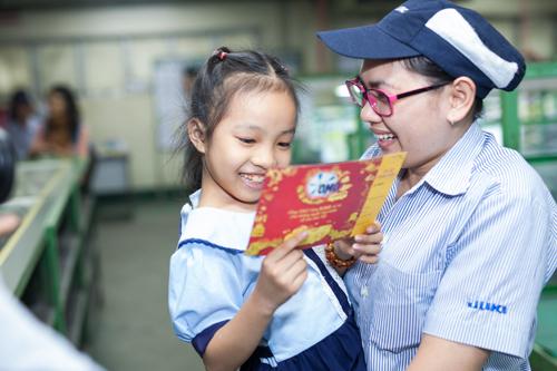 Học sinhtrường tiểu học Trần Nhân Tôn (quận 10, TP HCM) trao tặng các cô chú công nhân công ty Juki tại khu chế xuất Tân Thuận.