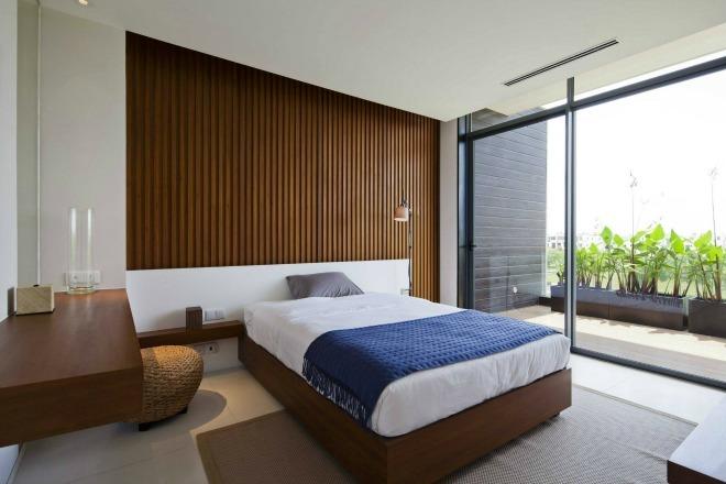 Phòng ngủ sử dụng đồ nội thất gỗ mộc, cửa sổ kính nhìn ra khoảng sân xanh bóng cây.