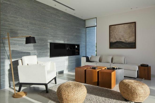 Không gian dành riêng cho việc tiếp khách sử dụng đồ nội thất chất liệu tự nhiên như bàn gỗ, đèn gỗ, ghế và thảm đan bằng lục bình và cói.