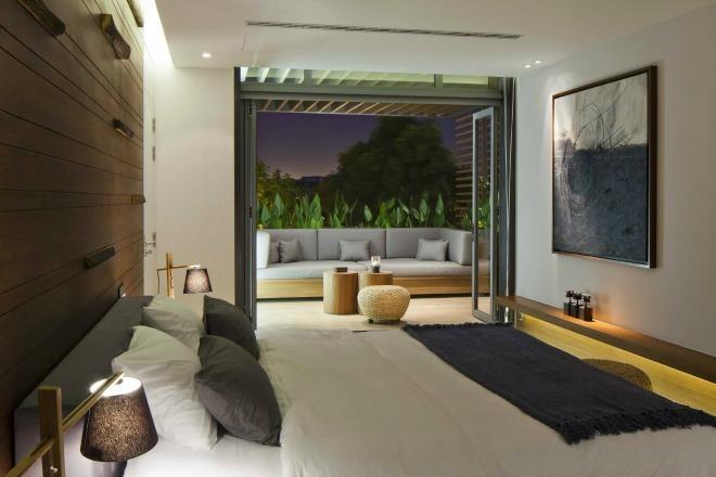 Ở tầng trên cùng là hai phòng ngủ sử dụng chung một nhà tắm và một sân thượng với những ghế nằm được bao bọc bởi những mảng cây xanh nhiệt đới.