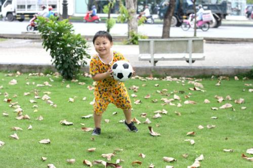 Bé chơi đá bóng.