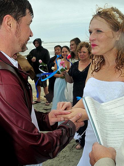 Anh Joyevà chị Judy Scruggs trao lời thề nguyền bên nhau trọn đời giữa trời mưa bão, bên bờ biển. Ảnh: People.