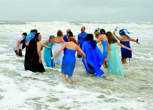 Cả cô dâu chú rể và khách đều thích thú xuống biển vui đùa dù thời tiết xấu.Ảnh: People.