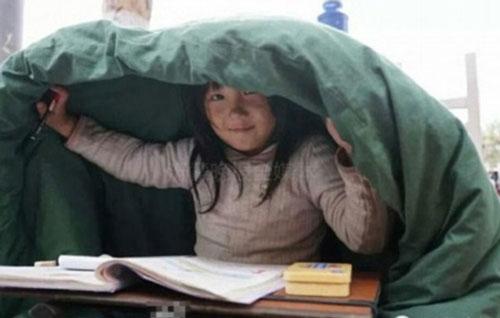 Em bé 6 tuổi vừa ăn xin vừa học bài trên vỉa hè