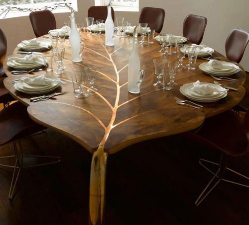 Chiếc bàn hình chiếc lá với vân màu đồng khiến cho phòng ăn trở nên khác biệt
