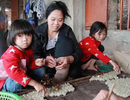 Ngoài nghề chính thông tâm sen được 10.000 đồng mỗi ngày, ba mẹ con chị Tỉnh có thêm nghề thời vụ là xoáy long nhãn, mỗi ngày được 60.000 đồng.Ảnh:Phan Dương.