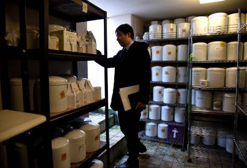 Nhânviên nghĩa trang kiểm tra hàng trăm phần tro cốt không ai nhận được lưu trữ trong căn phòng dưới lòng đất tại nghĩa trang ở thành phốSaitama, Nhật Bản. Ảnh: Japantimes.