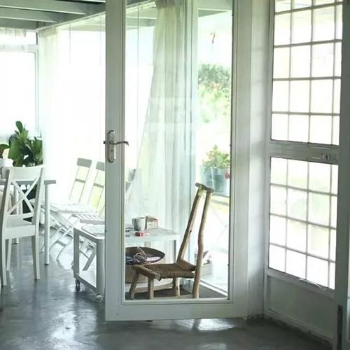 Ngôi nhà mang nét kiến trúc Bắc Âu với hầu hết đồ dùng mang tông màu trắng, sàn láng xi măng. Nhà nằm trong không gian rộng hàng trăm m2 nên có thể thoải mái mở cửa kính ở nhiều phía.