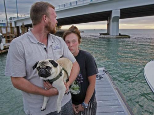Anh Tanner Broadwell ôm chú chó của mình bên cạnh người yêu trên bãi biển sau khi chiếc thuyền hai người dành tất cả tiền bán hết đồ đạc để mua bị đắm. Ảnh: AP.