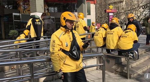 Anh Wang Junqiang đang kiểm tra điện thoại, đợi nhận đơn đặt hàng tiếp theoở góc một trung tâm thương mại náo nhiệt tại quậnXujiahui, Thượng Hải. Ảnh: Scmp.