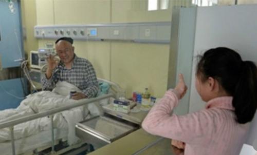 Lần gần đây nhất đến thăm bố, Zhenzhen đã giơ ngón cái lên qua cửa kính thể hiện sự quyết tâm cùng bốchiến đấu với căn bệnh trong ca mổ tới. Ảnh: Scmp.