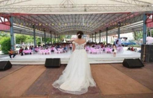 Ảnh: Cô dâuJutathip đứng trên sân khấu thông báo với khách mời chú rể không tới đám cưới. Ảnh: Facebook.