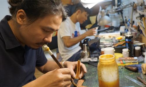 Anh Cao Duy Long (trái) và cộng sự duy nhất cặm cụi làm dây đồng hồ da trong căn xưởng nhỏ xíu của mình ở phố Liên Trì (Hoàn Kiếm, Hà Nội).Ảnh:Trọng Nghĩa.