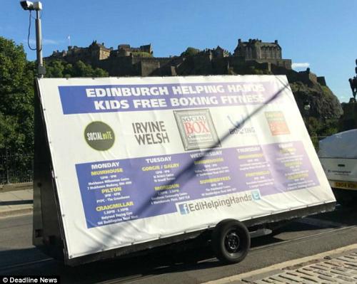 Chiếc xe từ thiện kéo theo tấm biểu ngữ trong đó giúp trẻ em có thể đến học các lớp học võ miễn phí ở Edinburgh.