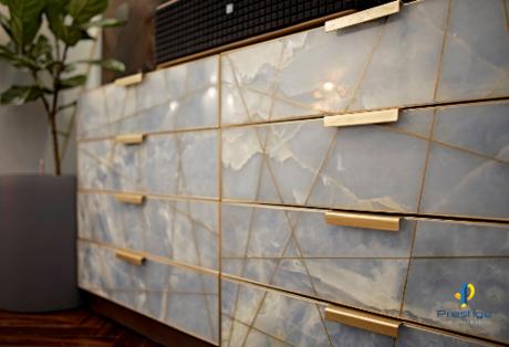 Tủ để tivi là đá cẩm thạch xanh da trời, được rạch tay khéo léo ngàm chặt chỉ đồng theo từng đường ngang dọc phá cách trong thớ đá, tinh xảo, đặc biệt. Gia chủ có để để điều khiển tivi, điều khiển điều hòa...trong các ngăn để giúp ngôi nhà gọn gàng hơn.