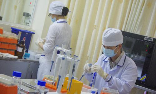 Các chuyên viên đang xử lý mẫu xét nghiệm tạiTrung tâm phân tíchADN và công nghệ di truyền. Ảnh: NT.
