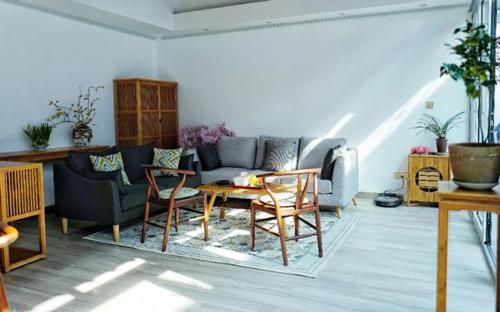 Không gian phòng khách tạo cảm giác gần gũi, ấm cúng nhờ bộ ghế sofa kết hợp bàn ghế gỗ. Những chậu cây nhỏ xinh tạo thành điểm nhấn tinh tế cho ngôi nhà.