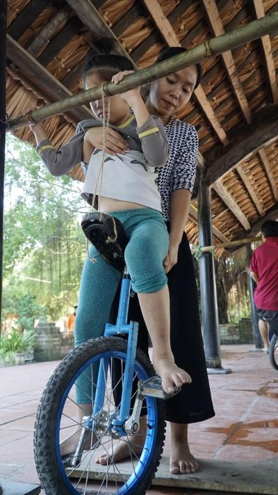 Với học viên Hà Chi, Dungmất 8 tháng để huấn luyện bé ngồi lên được xe đạp một bánh. Ảnh: Trọng Nghĩa.