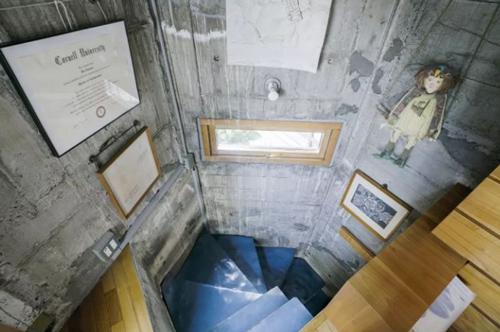 Cầu thang nhỏ xoắn ốc chỉ đủ một người bước. Trên tường được kiến trúc sư khéo léo trang trí bằng những bức tranh, bằng khen... xua đi cảm giác ảm đạm, đơn điệu của màubê tông. Các phòng trong nhàriêng lẻ, xếp chồng lên nhau mà không có cửa ngăn, phòng tắm cũng chỉ được ngăn cách bằng rèm cửa.