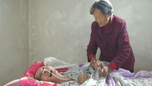 Anh Wang Shubao tỉnh dậy nhìn thấy dòng nước mắt lăn dài trên gương mặt người mẹ già đã chăm sóc anh hơn một thập kỷ qua. Ảnh: Jining News Network.