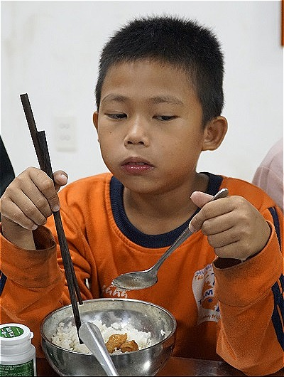 Tự giác ăn cơm là một trong những thay đổilớnnhất trong đời của cậu bé 8 tuổi. Ảnh: Trọng Nghĩa.