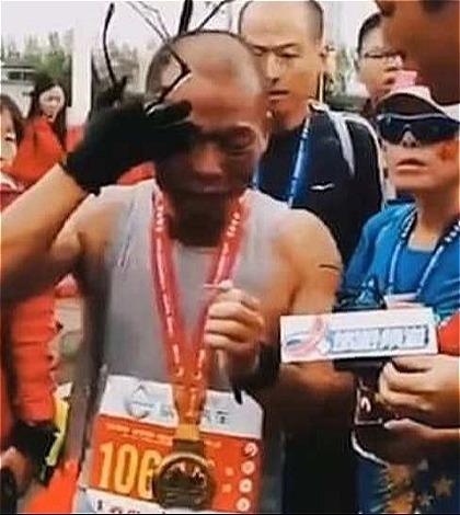 Anh Li òa khóc và nhìn tấm di ảnh của con trai khi về đích. Ảnh: China News.