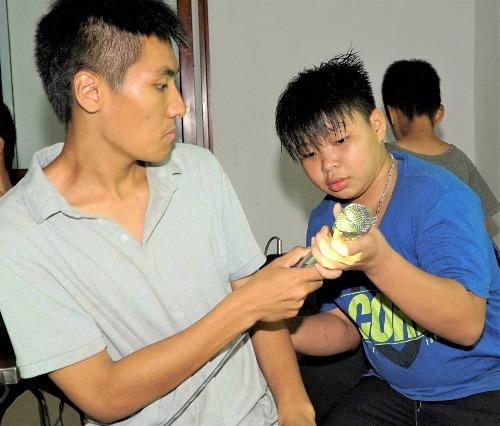 Quá trình dạy học viên Trọng (trái) nói và hát làkhó nhất, buộc Phú nhiều khi phải lớn tiếng để bạn tập trung. Ảnh: Trọng Nghĩa.